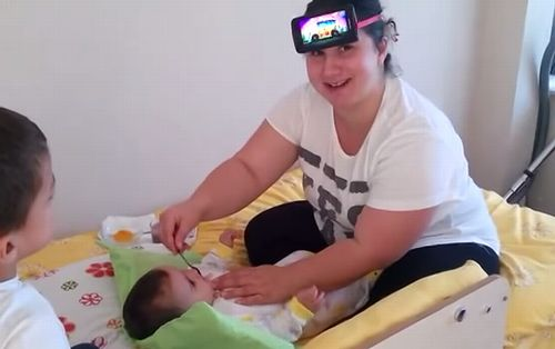 Feeding_Baby_with_Phone_on_head.jpg