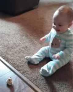 Cute_baby_laughs_at_flipping_toy.png