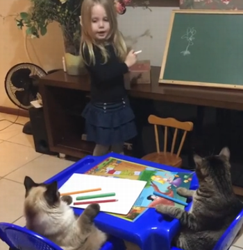 Little_girl_teaching_her_cats.png
